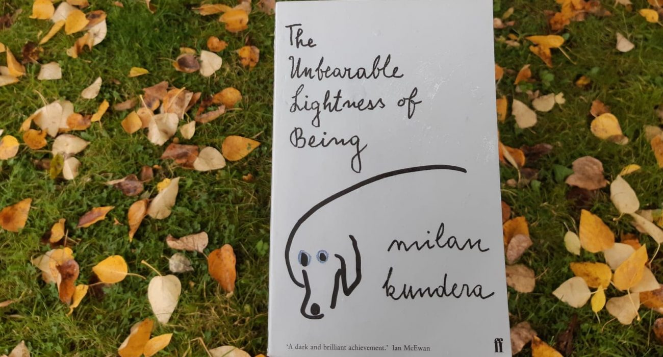 Photo of The Unbearable Lightness of Being by Milan Kundera against the backdrop of leaves