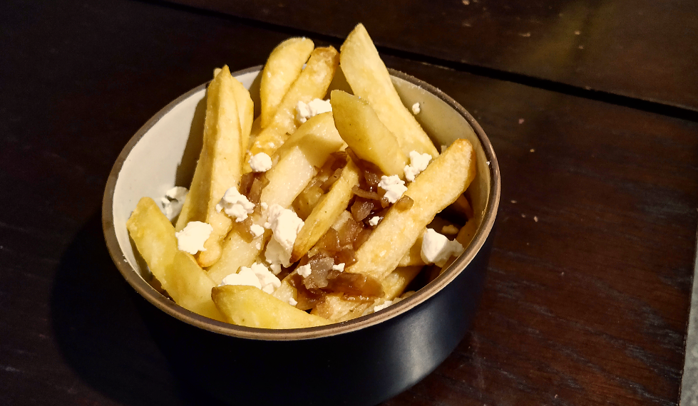 chips in a bowl with onion gravy and goats cheese on top