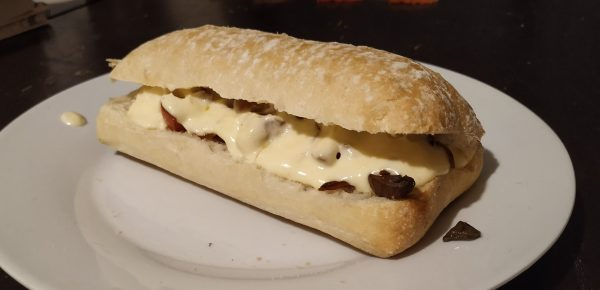 ciabatta roll with veg and gooey cheese sauce