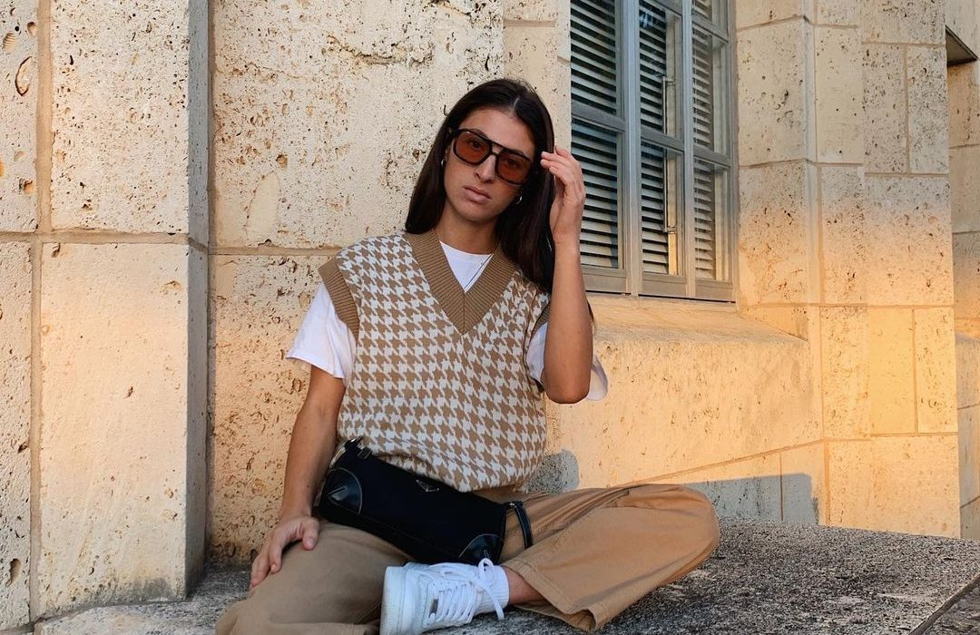 Woman wearing beige and white sweater vest with t-shirt and trousers