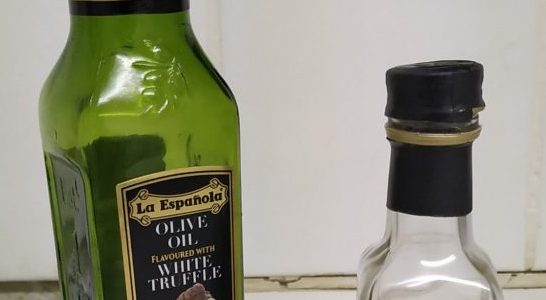 one larger bottle of La Espagnola truffle oil next to a smaller bottle of M and S truffle oil
