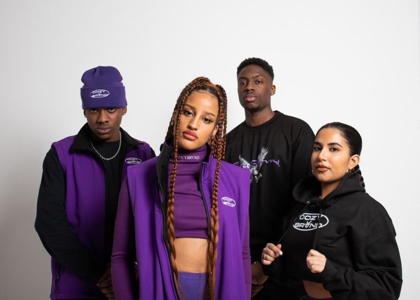 Two female models and two male models wearing the Cozybrvnd's newest streetwear collection in purple and black