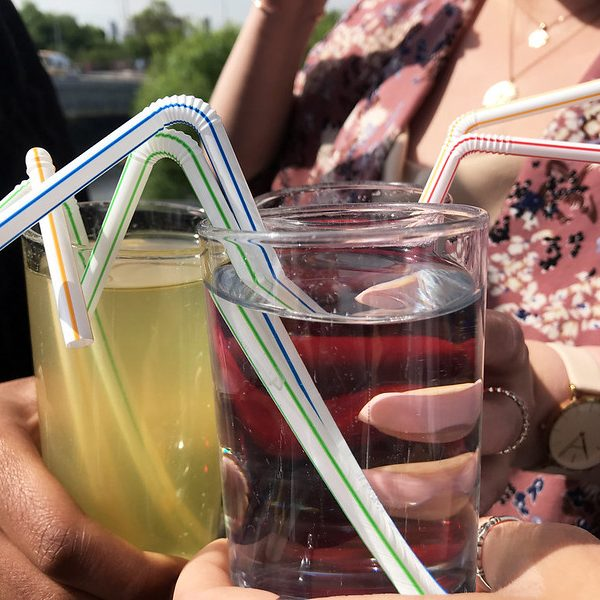 people holding three glasses with coloured drinks and plastic straws