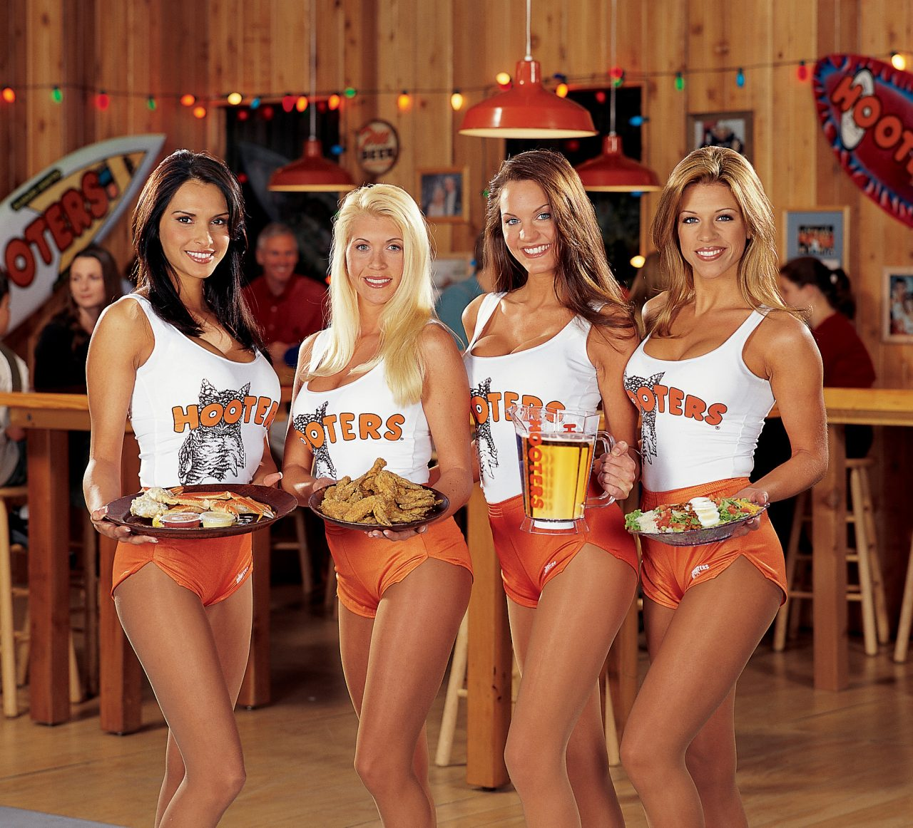 Hooters waitresses holding food and beer. Used to depict UoM staff expenses spending in 2019.