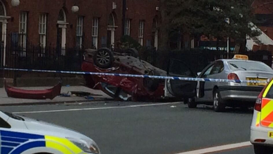 A red Lexus was overturned, with two trapped inside, after colliding with a taxi. Photo: Michael Williams