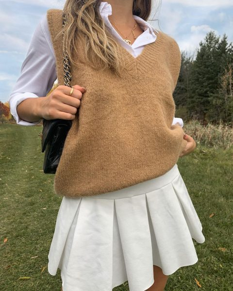 Brown sweater vest with white collar and pleated skirt