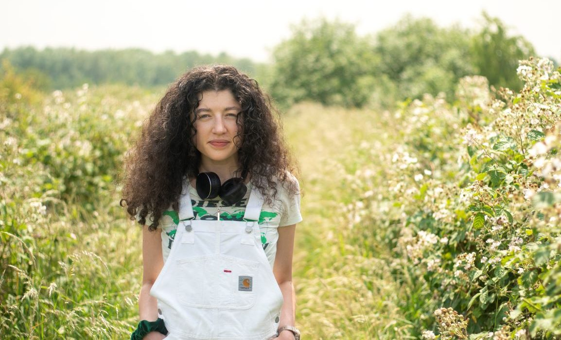 striking white dungarees and green floral background