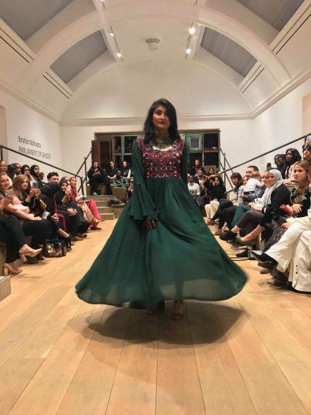 Model walking down catwalk in an emerald green dress by Electric Bazaar
