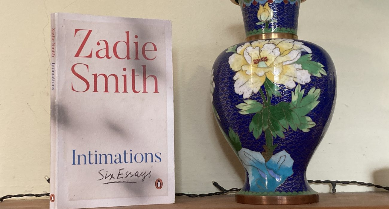 Intimations by Zadie Smith on a shelf next to a vase