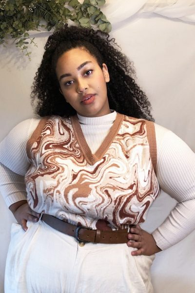Woman wearing marble sweater vest with cream jumper and brown belt