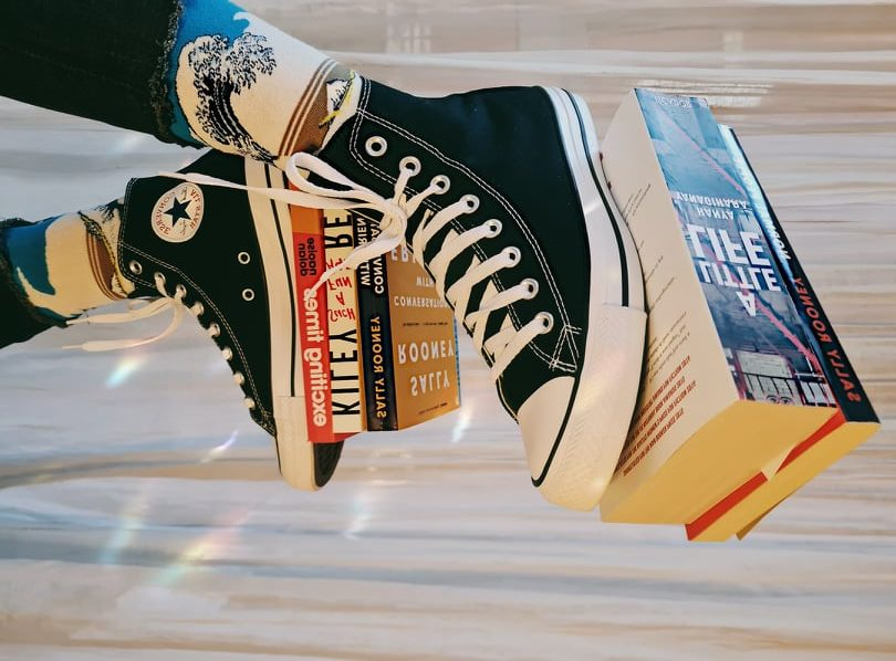 Martina's bookstagram bookshelf pic with a shot of books balanced on her trainers