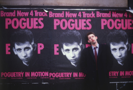 MacGowan stands before a commercial poster for punk band, The Pogues