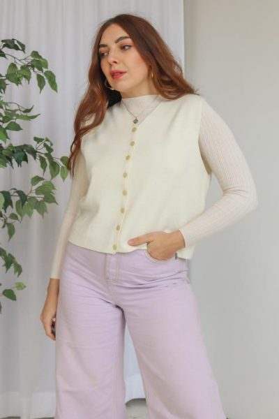 Woman wearing cream vintage sweater vest and lavender trousers