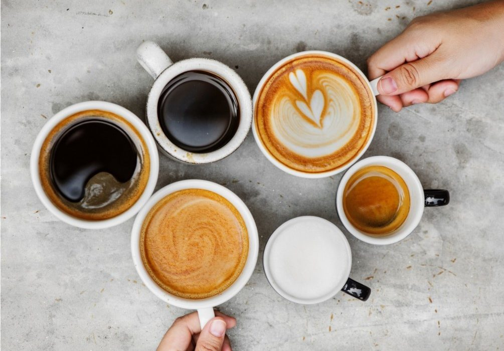 different types of coffee in six cups, with two hands holding two of the cups