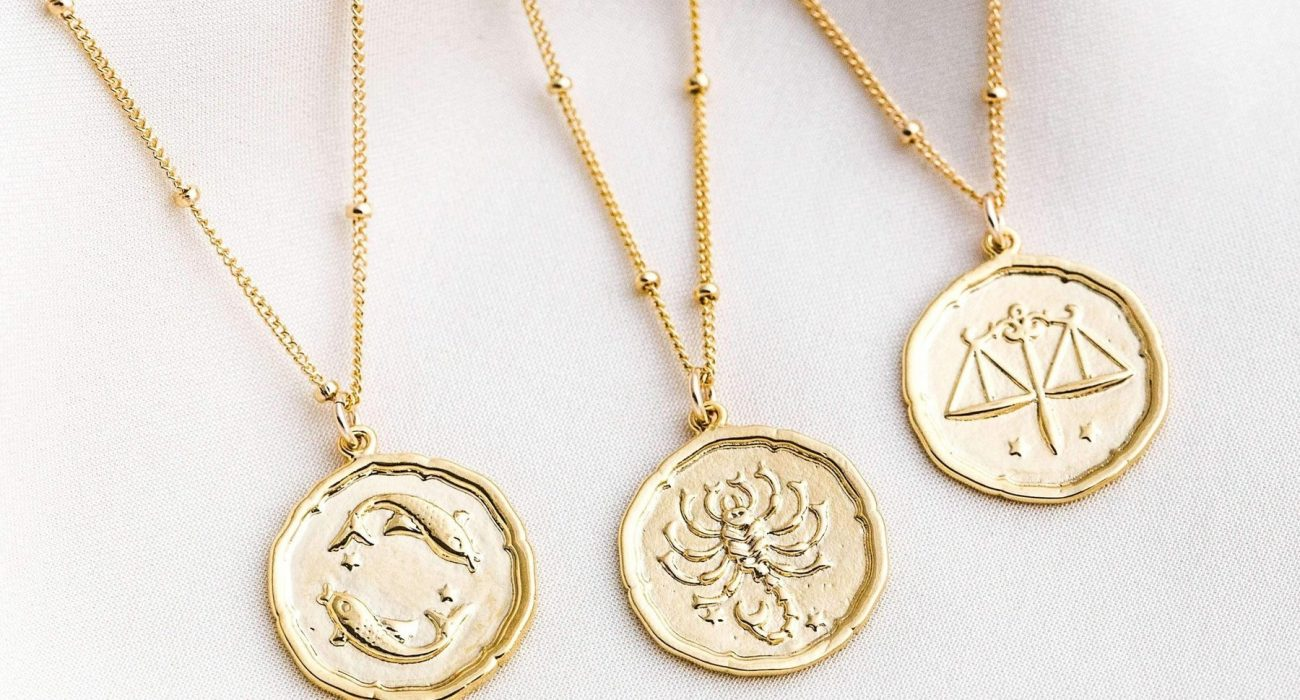 Gold pendant necklaces with zodiac sign prints
